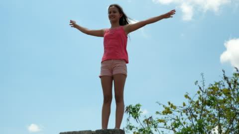 vidéos et rushes de r/f girl doing cartwheel while on tour of mayapan ruins with family - une seule petite fille