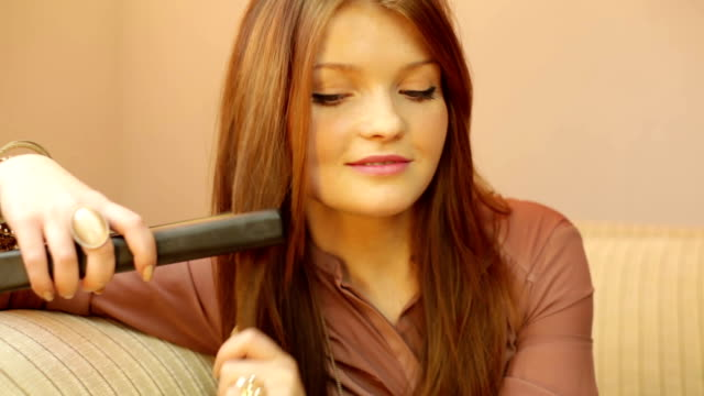 girl doing hairstyle with flat iron - hair straighteners stock videos and b-roll footage