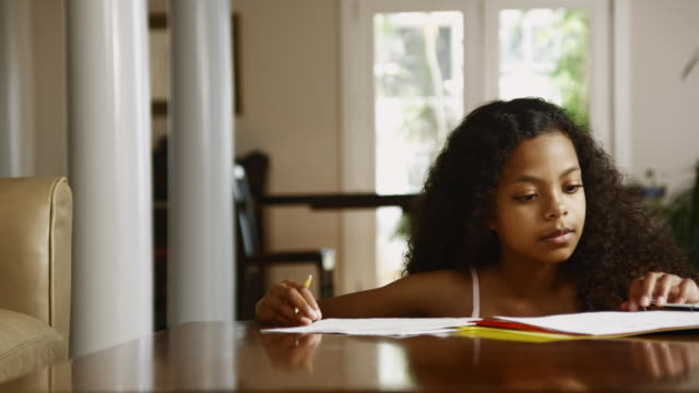 MS Girl (12-13) doing homework on dining table / Edmonds, Washington State, USA