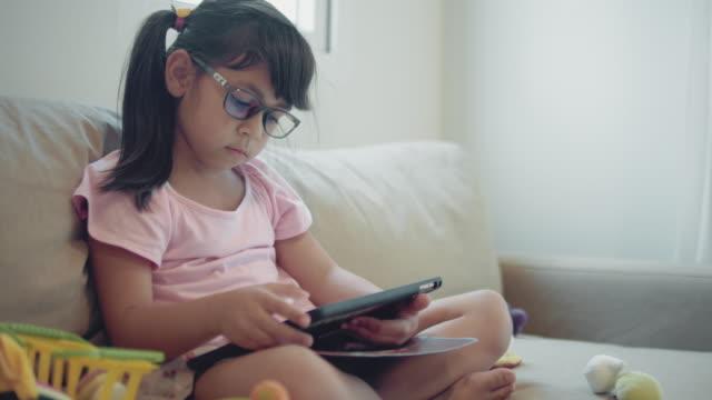 girl doing homework on tablet - cross legged stock videos & royalty-free footage