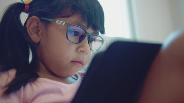 girl doing homework on tablet - home interior stock videos & royalty-free footage