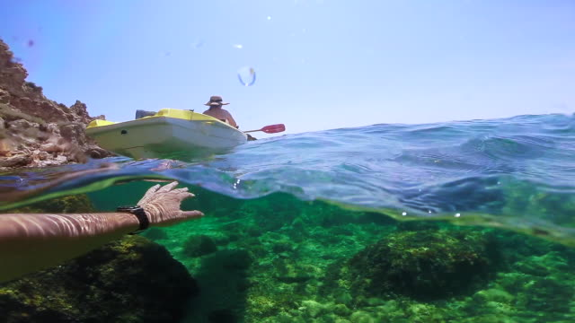Girl doing kayak exploring the Medes islands in the shoreline of Costa Brava Mediterranean Sea during summer vacations while boyfriend is recording from water in a paradise place recorded with dome and underwater view.