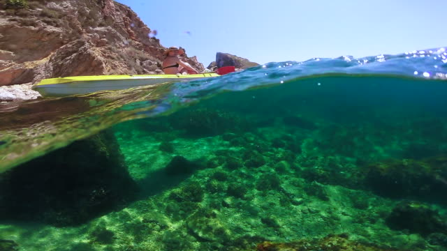 girl doing kayak exploring the medes islands in the shoreline of costa brava mediterranean sea during summer vacations in a paradise place recorded with dome and underwater view. - kayak stock videos & royalty-free footage