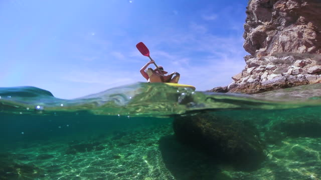 vídeos y material grabado en eventos de stock de girl doing kayak exploring the medes islands in the shoreline of costa brava mediterranean sea during summer vacations in a paradise place recorded with dome and underwater view. - kayak piragüismo y canotaje