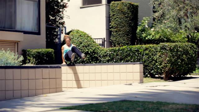 vídeos de stock, filmes e b-roll de garota fazendo parkour-pula, dá cambalhotas parede lateral - objeto manufaturado