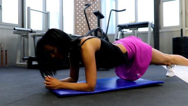 vídeos y material grabado en eventos de stock de chica haciendo flexiones en gimnasio - entrenamiento sin material
