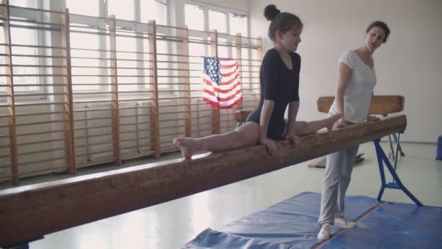 4K: meisje doen split op de evenwichtsbalk