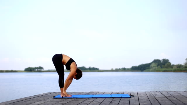 a girl doing yoga by the lake - sun salutation stock videos and b-roll footage
