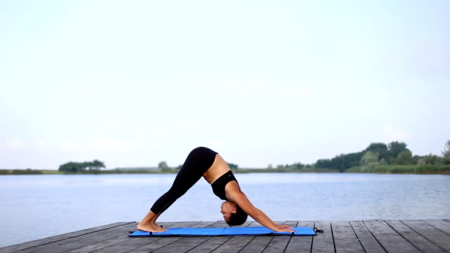 a girl doing yoga by the lake - sun salutation stock videos & royalty-free footage
