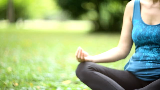 a girl doing yoga in the park - lotus position stock videos & royalty-free footage