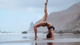 Girl doing yoga on the shore of the ocean on the beach standing in a pose bridge on his hands