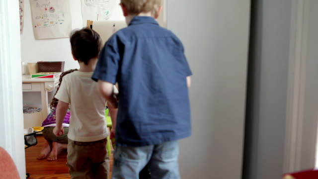 WS Girl (6-7) drawing at easel in play room, boys (2-5) taking toys away / Brooklyn, New York City, USA