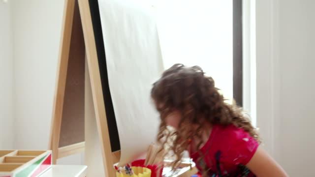 MS Girl (6-7) drawing at easel in playroom / Brooklyn, New York City, USA