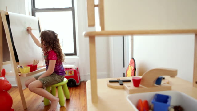 WS Girl (6-7) drawing at easel in playroom / Brooklyn, New York City, USA