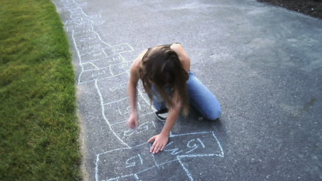 ws girl drawing hopscotch with colored chalk on sidewalk / langley, british columbia, canada.  - gessetto da lavagna video stock e b–roll