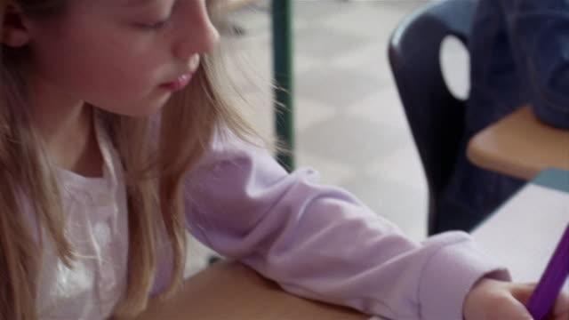 vídeos y material grabado en eventos de stock de girl drawing picture of elephant with purple marker in class / gorham, maine - a la izquierda de