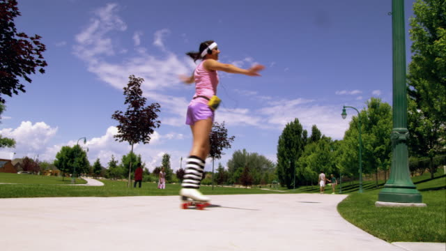 girl dressed in 80's athletic clothing roller skating in the park. - knee highs stock videos and b-roll footage