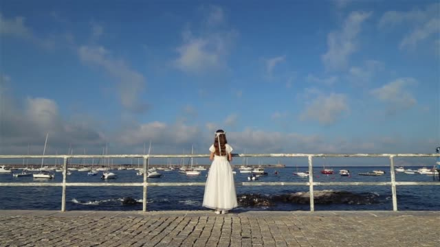 girl dressed in white standing back looking at the sea in a harbor. - kopfsteinpflaster stock-videos und b-roll-filmmaterial