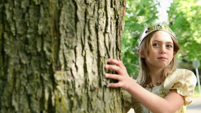 Girl dressed up as queen touching tree trunk