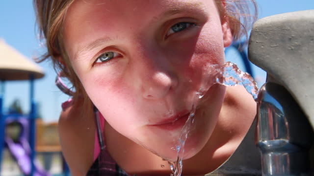 CU Girl drinking from water fountain / Tracy, CA, United States