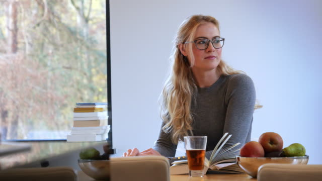 vídeos y material grabado en eventos de stock de muchacha de beber té caliente y lectura - magazine