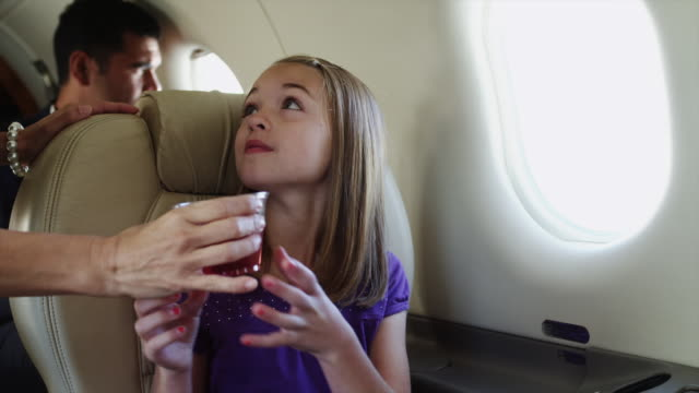 ms girl (10-11) drinking juice in airplane / spanish fork, utah, usa - juice drink stock videos & royalty-free footage