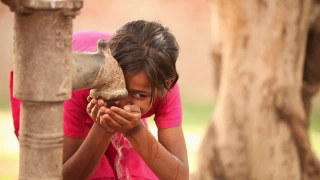Girl drinking water from handpump, Faridabad, Haryana, India