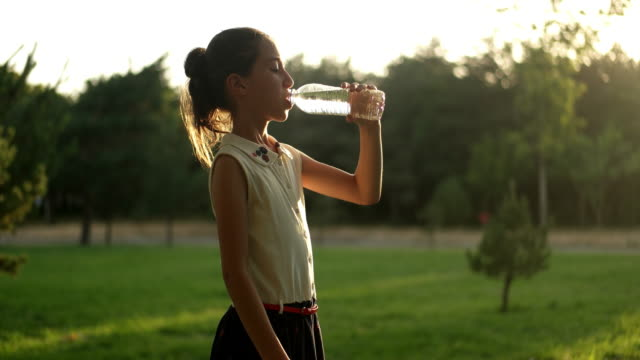 girl drinking water outdoors - bottiglia video stock e b–roll