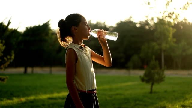 mot - mädchen trinkwasser im freien zu verlangsamen - wärme stock-videos und b-roll-filmmaterial