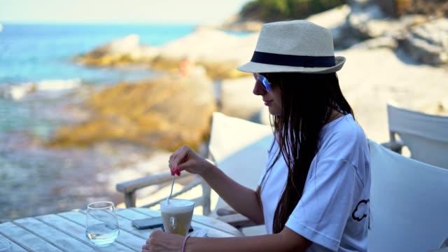 vídeos de stock, filmes e b-roll de garota bebe café em um bar de praia - grécia