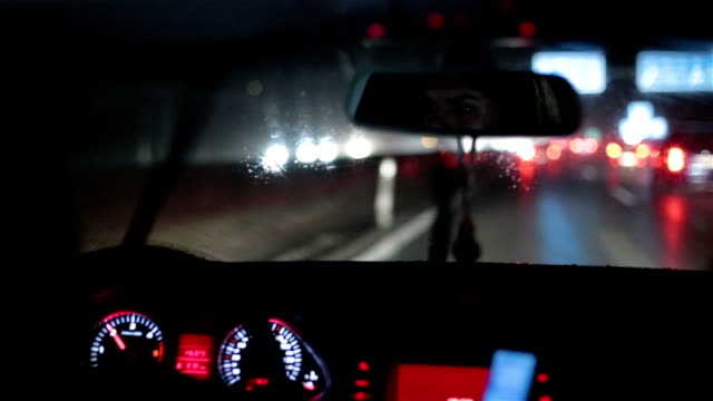 girl driving a car on a rainy night - rear view mirror stock videos and b-roll footage