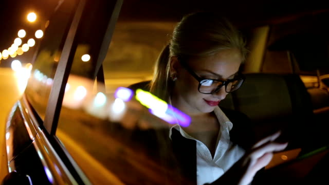 girl driving at night in the taxi - occhiali da vista video stock e b–roll