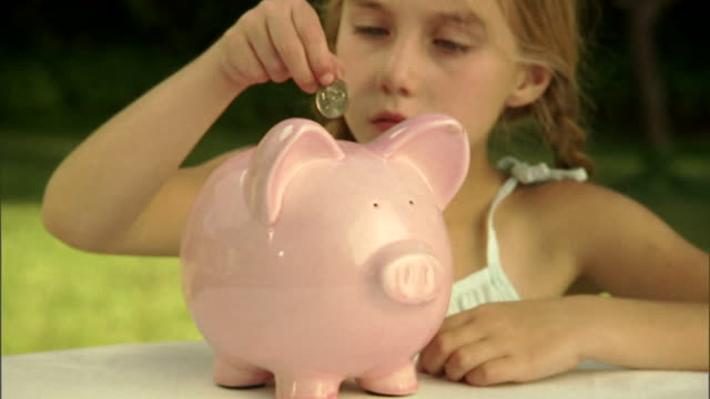 cu, girl (6-7) dropping coins into piggy bank - piggy bank stock videos & royalty-free footage