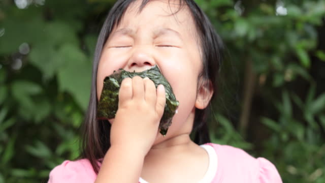 girl eating a rice ball outdoors - rice ball stock videos & royalty-free footage