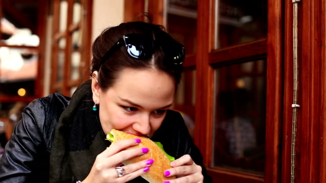 girl eating a sandwich and wipes her lips - sandwich stock videos & royalty-free footage