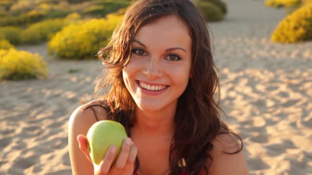 Girl eating apple on beach