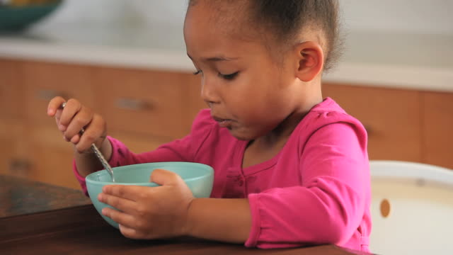 CU TU Girl (2-3) eating bowl of cereal at table / Richmond, Virginia, USA