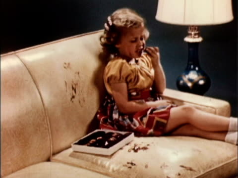 1956 ms girl eating boxed chocolates on leather sofa, sofa is stained with chocolate fingerprints / usa - unfug stock-videos und b-roll-filmmaterial