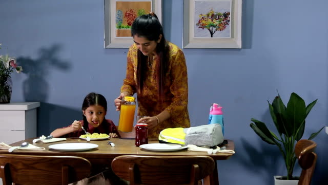 girl eating breakfast with her mother, delhi, india - zaino da montagna video stock e b–roll