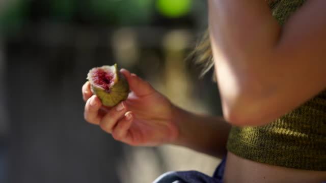 girl eating fig from tree - frutta video stock e b–roll