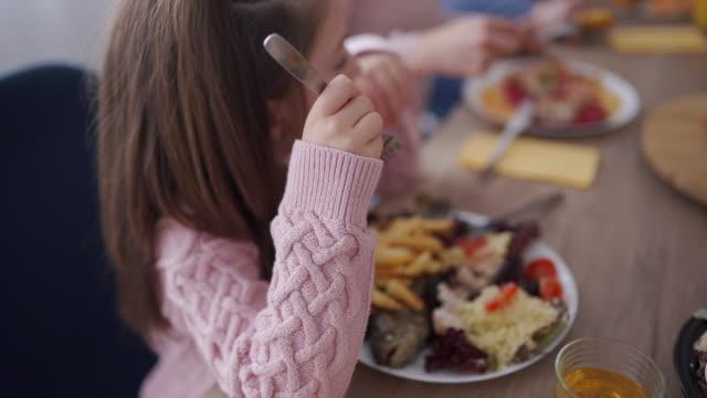 vidéos et rushes de fille mangeant le poisson pendant le déjeuner de famille - famille avec un enfant