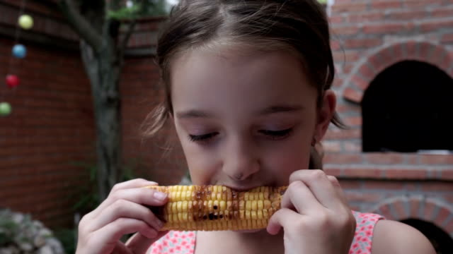 Girl eating grilled corn