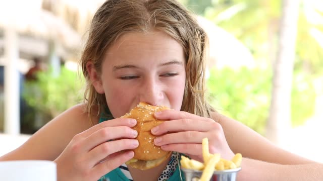 girl eating hamburger - hamburger stock videos and b-roll footage