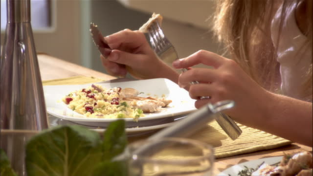 stockvideo's en b-roll-footage met girl eating healthy lunch with family at kitchen table - tafelmanieren