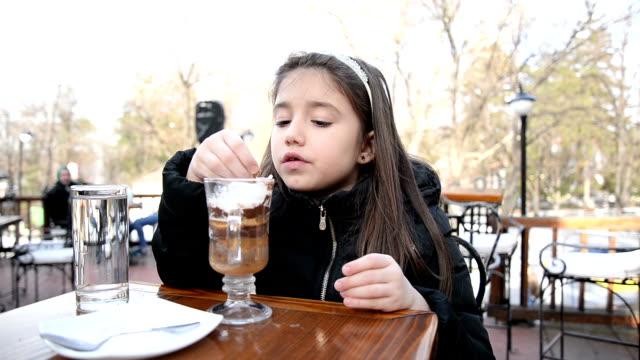 Girl eating hot chocolate.