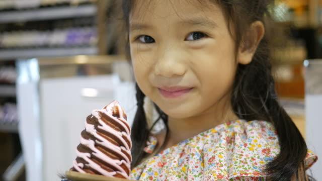 stockvideo's en b-roll-footage met meisje ijsje eten - likken