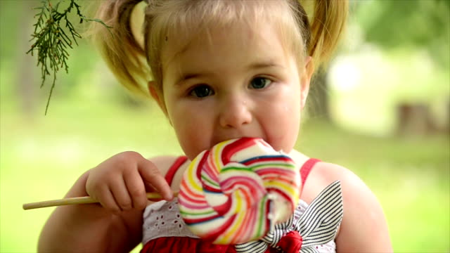 girl eating lollipop. slow motion. - lollipop stock videos and b-roll footage