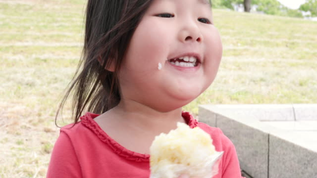 girl eating rice ball in the park - rice ball stock videos & royalty-free footage
