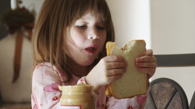 CU Girl (4-5) eating sandwich in kitchen / Cedar Hills, Utah, USA