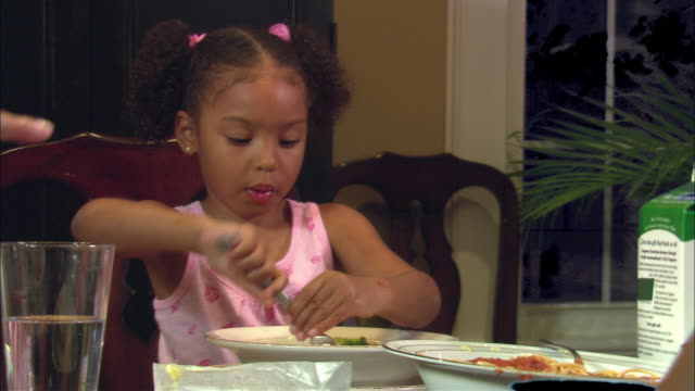 MS, girl (4-5) eating spaghetti at dinner table, Westfield, New Jersey, USA